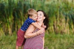 Jongen die zijn zwangere moeder kussen royalty-vrije stock foto's