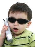Jongen die in Zonnebril op de Telefoon over Wit spreekt stock fotografie