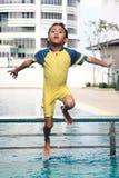 Jongen die in Zwembad springt Stock Afbeeldingen
