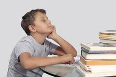 Jongen door boeken met dromerige gesloten die ogen wordt omringd Stock Foto's