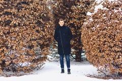 jongen in een de winterjasje onder de de winterbomen royalty-vrije stock foto's