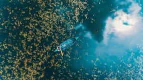 Jongen in een kano door weerspiegelend meer wordt omringd dat stock foto