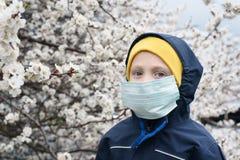 Jongen in een medisch beschermend masker in openlucht Bloeiende boom, de lentedag stock foto