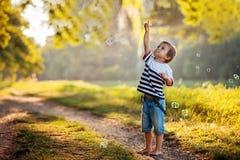 Jongen in een park, die met zeepbels spelen Royalty-vrije Stock Afbeeldingen
