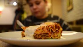 Jongen in een restaurant met een plaat van lasagna's stock videobeelden