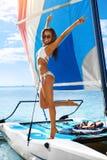 Jongen en de meisjes die bij het surfen van bureau de zitten en kijken op blauwe overzees Gelukkige Vrouw die van de Vakantie van Stock Afbeelding