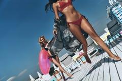Jongen en de meisjes die bij het surfen van bureau de zitten en kijken op blauwe overzees Royalty-vrije Stock Fotografie