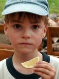 Jongen en een plak van citroen stock foto