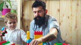 Jongen en gebaard mensenspel samen Familie en kinderjarenconcept De vader en de zoon creëren kleurrijke bouw met stuk speelgoed stock videobeelden