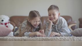 Jongen en het meisje van portret liggen de aanbiddelijke kleine tweelingen op het tapijt en het letten van op iets die grappig op stock video