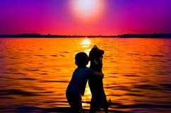 Jongen en hond bij zonsondergang Royalty-vrije Stock Fotografie
