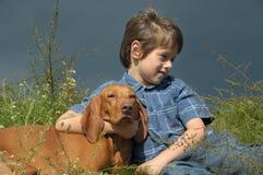 Jongen en Hond in de Weide Royalty-vrije Stock Afbeeldingen
