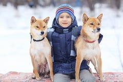 jongen en honden in de winterpark Royalty-vrije Stock Afbeelding