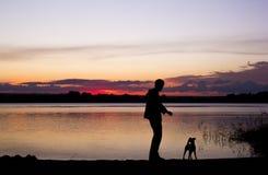 Jongen en hondsilhouet bij zonsondergangmeer Stock Fotografie