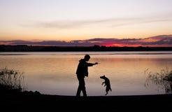 Jongen en hondsilhouet bij zonsondergangmeer Royalty-vrije Stock Foto's