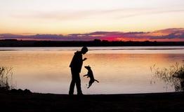 Jongen en hondsilhouet bij zonsondergangmeer Royalty-vrije Stock Fotografie
