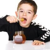 Jongen en honing Stock Fotografie