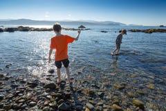 Jongen 7 en jongen 9 peddel in het overzees op de ochtend van de zomer in Onderbreking Royalty-vrije Stock Fotografie