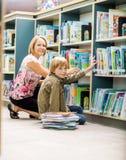 Jongen en Leraars het Boekenrek van Selecting Books From Stock Foto
