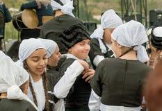 Jongen en leuke meisjes in traditionele Georgische kostuums die naar vieringspartij gaan Stock Afbeeldingen