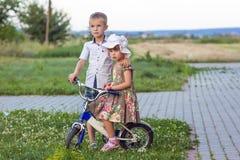 Jongen en meisje bij fiets het spelen in openlucht op een de zomer zonnige dag stock foto's