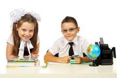 Jongen en meisje bij het bureau Stock Afbeeldingen