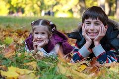 Jongen en meisje in de zonnige zitting van het de herfstpark op bladeren Royalty-vrije Stock Foto's
