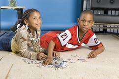 Jongen en meisje die aan een raadsel werken Stock Foto