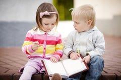 Jongen en meisje die aan notitieboekje schrijven Stock Foto
