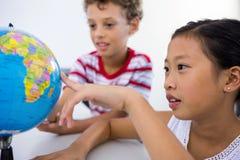 Jongen en meisje die glob in klaslokaal bekijken royalty-vrije stock afbeelding