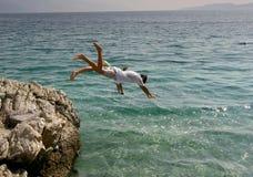 Jongen en meisje die in het overzees springen Royalty-vrije Stock Afbeelding