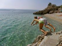 Jongen en meisje die in het overzees van de rotsen springen Stock Afbeelding