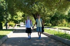 Jongen en meisje die in het Park in goed weer na school lopen royalty-vrije stock afbeeldingen