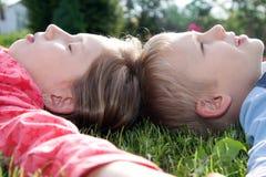 Jongen en meisje die op gras leggen Stock Foto's
