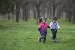 Jongen en meisje die in park lopen stock foto's