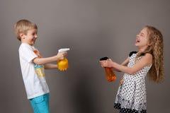 Jongen en meisje die water spuiten stock afbeeldingen