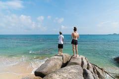 Jongen en meisje die zich in afstand op grote rots op water` s rand bevinden Stock Foto's