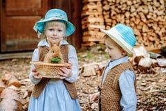 Jongen en meisje in dorp het spelen met de konijnen stock foto's
