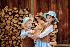Jongen en meisje in dorp het spelen met de konijnen royalty-vrije stock fotografie
