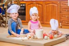 Jongen en meisje en een pasgeboren jong geitje met hen in chef-kok` s hoeden die op de keukenvloer zitten die met bloem wordt bev stock foto