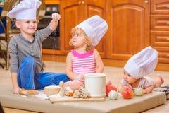 Jongen en meisje en een pasgeboren jong geitje met hen in chef-kok` s hoeden die op de keukenvloer zitten die met bloem wordt bev stock fotografie