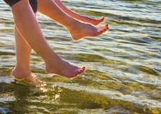Jongen en meisje geladen voeten in het water op een zonnige dag Royalty-vrije Stock Foto