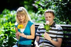 Jongen en meisje met bloemen op een romantische datum Stock Foto