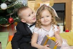 Jongen en meisje met giften dichtbij de Kerstboom Royalty-vrije Stock Foto