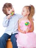Jongen en meisje met lollys Stock Foto's