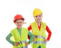 Jongen en meisje met weerspiegelende vest en helm stock foto's