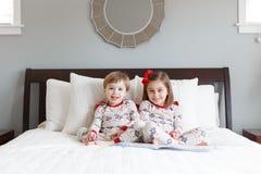 Jongen en meisje op bed met Kerstmispyjama's royalty-vrije stock foto