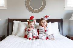Jongen en meisje op bed met Kerstmispyjama's royalty-vrije stock fotografie
