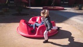 Jongen en meisje op een kleine carrousel stock videobeelden