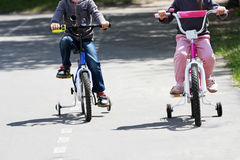 Jongen en meisje op fietsen Stock Afbeeldingen